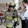 Danvers:<br /> Matt Blank, left, eighth grader at the Holten-Richmond Middle School, gets suited up in firefighter gear with the help of Deputy Chief Kevin Farrell. Matt witnessed the weight and bulk of the equipment used by a firefighter when he crawled on his hands and knees and crawled under a desk in the classroom. Deputy Chief Kevin Farrell was one of the speakers at the career day at the school.<br /> Photo by Ken Yuszkus/Salem News, Thursday, March 12, 2009.
