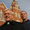 Peabody:<br /> Rev. John MacInnis, left, and John Stueve, owner of the construction company that did the repairs and renovations on the steeple, plus he is the property manager, stand in front of St. John the Baptist Church early Fiday morning.<br /> Photo by Ken Yuszkus/Salem News, Friday,  December 3, 2010.