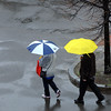 Salem:<br /> Two pedestrians with umbrellas walk in the rain on Church Street in Salem.<br /> Photo by Ken Yuszkus/Salem News, Wednesday, April 13, 2011.