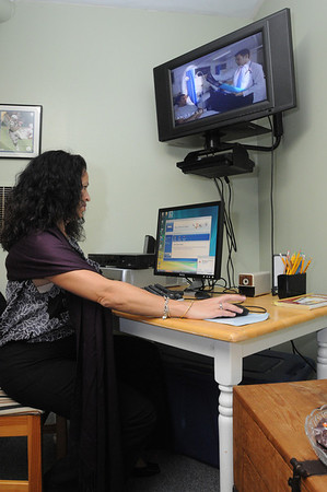 Salem:<br /> Parole officer Kim Lawrence works on the  computer near the television, both donated, at the Community Resource Center which is opening for at-risk youth.<br /> Photo by Ken Yuszkus/Salem News, Thursday, October 20, 2011.