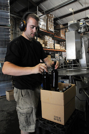 Ipswich:<br /> Jack Rogers places the filled 22ounce bottles of beer into cardboard boxes at the filler machine at the Ipswich Ale Brewery.<br /> Photo by Ken Yuszkus/Salem News, Friday, June 11, 2010.