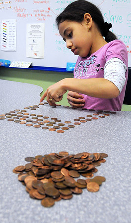 Salem:<br /> Juliza Reyes counts out a hundred pennies in rows of ten to add to the total for the Pennies for Peace. The first and second graders at the Bates School will give the final amount to Greg Mortenson when he comes to Salem on May 1 to accept the Salem Award.<br /> Photo by Ken Yuszkus/Salem News, Friday, April 16, 2010.