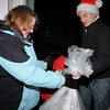 Beverly:<br /> Dawn Trethaway receives a bag of gifts from Justin Isabella of Beverly. Besides gift giving, Christmas carols were sung by the group walking in the Gloucester Crossing neighborhood.<br /> Photo by Ken Yuszkus/Salem News, Tuesday, December 22, 2009.