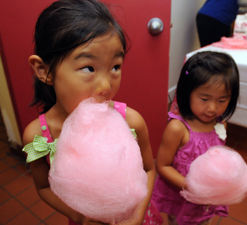 Salem:<br /> Anna Kim, left, 5, and her sister Julia Kim, 3, both of Beverly, dive into some cotton candy during the Kids Night on the Common which is part of Heritage Days. Rain forced the event inside the Salem YMCA instead of holding it on the Salem Common.<br /> Photo by Ken Yuszkus/The Salem News, Friday, August 10, 2012.