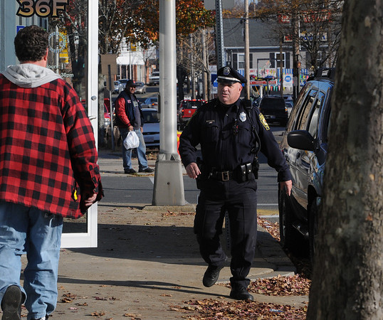 Peabody:<br /> Bob Mahoney, Peabody police officer, greets a pedestrian as he walks down Walnut Street as part of his patrol route.<br /> Photo by Ken Yuszkus/Salem News, Wednesday November 18, 2009.