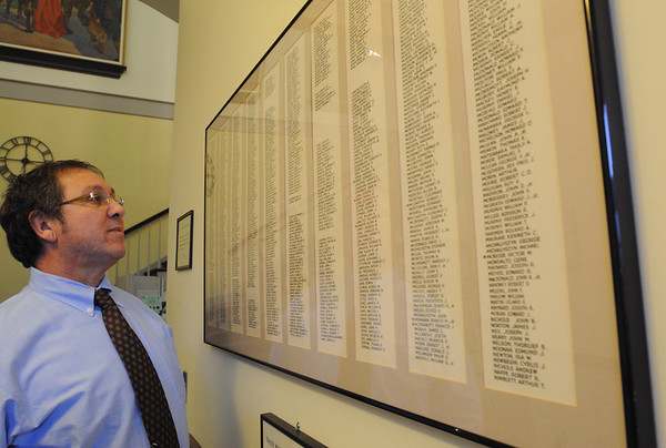 Danvers:<br /> Peter Mirandi, Danvers Veterans Agent and town's director of public health, stands near one of the two framed World War II roll call of rememberance lists which has been hung back up in the Town Hall.<br /> Photo by Ken Yuszkus/Salem News,  Monday,  November 8, 2010.