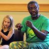 Middleton:<br /> Bailey Cloutier, 7, sits with Otha Day in front of the audience while he instructs them in hand rhythm at the Flint Public Library during his program, Otha Day's Drumming to the Beat.<br /> Photo by Ken Yuszkus/Salem News, Tuesday, August 2, 2011.