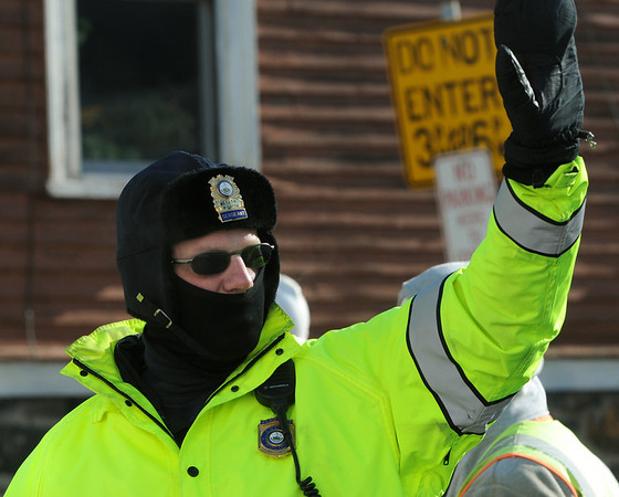 Salem:<br /> Sergeant Marc Berube directs traffic at his work detail on Bridge Street. Sergeant Marc Berube wears protective clothing to shield him from the strong frigid wind that hit the area Friday. <br /> Photo by Ken Yuszkus/Salem News, Friday, January 29, 2010.