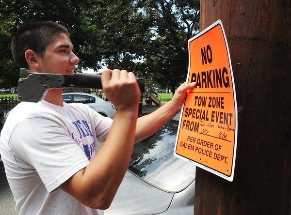 Salem:<br /> Dan Dobrosielski of the Salem traffic department posts one of many signs on Washington Square East near the Salem common banning parking on Tuesday and Wednesday for the upcoming events during Heritage Days.<br /> Photo by Ken Yuszkus/Salem News, Monday, August 6,  2012.