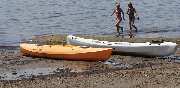 Beverly:<br /> Katelyn White, left, and Hannah Smith walk in the water past two beached kayaks at the beach at Lynch Park.<br /> Photo by Ken Yuszkus/Salem News, Monday, June 27, 2011.