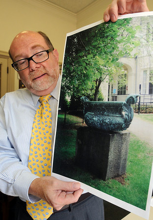 Danvers:<br /> Doug Rendell, director of the Danvers Peabody Institute Library, holds an image of the large urn that was on the library's property which was stolen and recovered recently.<br /> Photo by Ken Yuszkus/Salem News, Monday August 9, 2010.