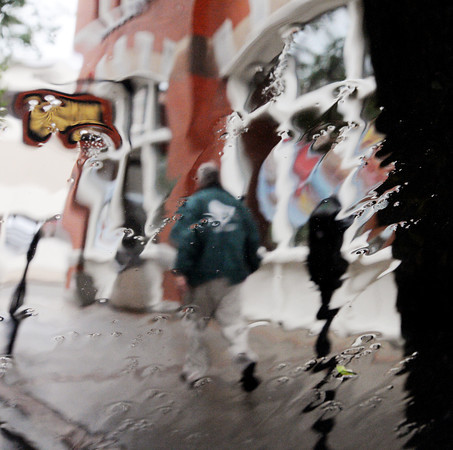Beverly:<br /> A pedestrian walks in the rain on Cabot Street as seen through a rain coated car windshield. Rain will continue for the next few days.<br /> Photo by Ken Yuszkus/Salem News, Monday, June 4, 2012.