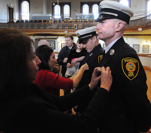 Peabody:<br /> Timothy O'keefe, far right, gets pinned by his wife, Ann-Marie and Dale Kimball, second from the right, gets pinned by his wife, Stacy, during the swearing in ceremony at Peabody city hall on Wednesday morning. Two Peabody Fire fighters received promotions. Dale Kimball is promoted from fire Lt. to fire capt. and Timothy O'keefe is promoted from fire fighter to fire Lt.<br /> Photo by Ken Yuszkus/Salem News, Wednesday, February 9, 2011.