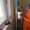 Salem:<br /> Toni Watson, Home Depot personnel, paints the pipes in one of the bedrooms on the second floor during the community renovation project at the Plummer Home for Boys in Salem on Thursday.<br /> Photo by Ken Yuszkus/Salem News, Thursday, April 21, 2011.