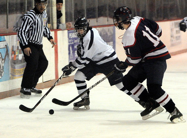 Peabody:<br /> Peabody's Mike Chiappini, left, controls the puck just before getting slammed into the boards during the Lincoln-Sudbury at Peabody boys hockey game at the McVann-O'Keefe Rink.<br /> Photo by Ken Yuszkus/Salem News, Monday, January 16, 2012.