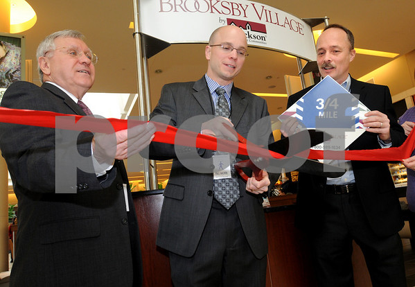 Peabody:<br /> From left, Peabody Mayor Michael Bofanti, John DeCetta, director of marketing, Brooksby Village, cutting the ribbon and Mark Whiting, mall general manager, at the ribbon cutting ceremony for the Mall Walking program at the Northshore Mall. The new program features branded mile-markers displayed on floor tiles around the mall to make it easy for mall walkers to track mileage and progress.<br /> Photo by Ken Yuszkus/Salem News, Wednesday,  February 25, 2009.