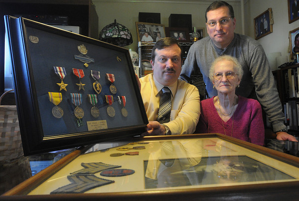 Salem:<br /> From left, Paul Verrette, son, Ruth Verrette, wife, and Phil Verrette, son, with framed medals, stripes, emblem, and a photo of WWII decorated veteran Philias Verrette who died last year in an accident.<br /> Photo by Ken Yuszkus/Salem News, Wednesday,  December 8, 2010.