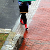 Salem:<br /> With her green umbrella and bright red boots a woman walks in the rain crossing Church Street in Salem.<br /> Photo by Ken Yuszkus/Salem News, Wednesday, April 13, 2011.