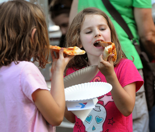 Salem:<br /> Adelaide Cutler, left, and her sister Harper Cutler, of Salem, wrestle to bite into slices of pizza during Salem's Best Pizza Competition at the Salem Common Monday night.<br /> Photo by Ken Yuszkus/Salem News, Monday, August 6,  2012.