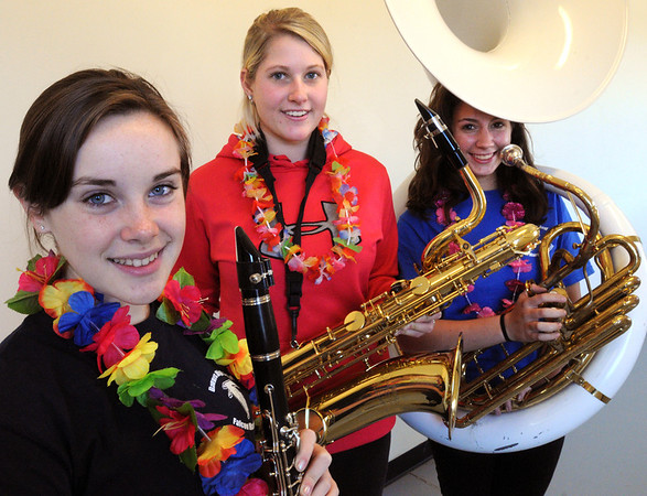 Danvers:<br /> From left, Maria Tenaglia with clarinet, Christina Parr with bari saxaphone, and Sarah Carey with sousaphone, are part of the Danvers High School band which is Hawaii bound. They are wearing leis for Hawaiian Day at the high school on Friday.<br /> Photo by Ken Yuszkus/Salem News, Friday, November 18, 2011.