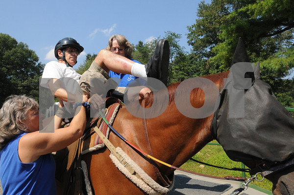 Topsfield:<br /> From left, Pam Skinner of Boxford, helps Don Summerfield of Cambridge, get on the horse, Clifford, with the help of Mandy Hogan of Beverly . The free program for physically disabled people to be able to ride a horse was held at the Bradley Palmer State Park.  <br /> Photo by Ken Yuszkus/Salem News Friday, September 05, 2008