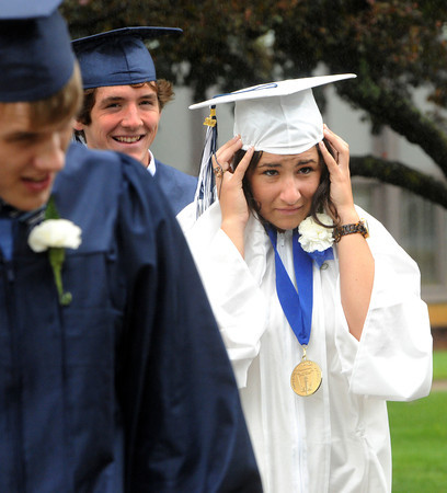 Wenham:<br /> Graduate Sophia Becker hangs onto her motarboard while walking in the light rain and wind during the procession into the Gordon College Chapel to start the Hamilton-Wenham Regional High School graduation held at Gordon College.<br /> Photo by Ken Yuszkus/Salem News, Sunday, June 3, 2012.