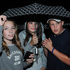 Salem:<br /> From left, Ali Szczechowicz, Cala Shairs, and Jack Crawley, all of Salem, sought refuge under an umbrella from a brief downpour. Lightning and thunder held up the start of the Peabody at Salem football season opener for an hour. It was held at Bertram Field in Salem.<br /> Photo by Ken Yuszkus/The Salem News, Friday, September 7, 2012.
