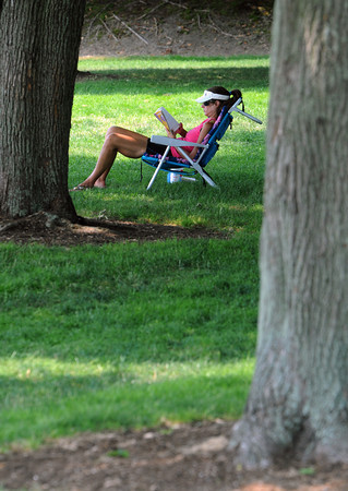 Beverly:<br /> Melissa Theriault of Beverly beats the heat by sitting in the cool shade of the trees with a slight breeze off the harbor reading a book at Dane Street Beach on Friday morning.<br /> Photo by Ken Yuszkus/Salem News, Friday, July 13,  2012.