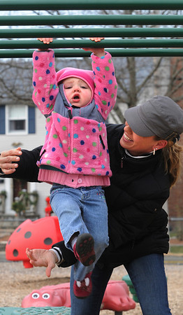 Beverly:<br /> Gabriella Nolan, 2, appears distressed as she tires from hanging from the bars of the playground equipment at the Cove Playground. Despite the drama, she returned to the bars several times. Her mother, April Clarizia, stands ready to help.<br /> Photo by Ken Yuszkus/Salem News, Friday, January 6, 2012.