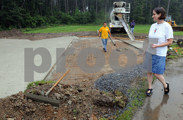 Beverly:<br /> Lauri Johnson, stands near the area where the truck just poured cement for the playground that will be  built at the North Beverly Elementary School.<br /> Photo by Ken Yuszkus/Salem News, Tuesday, July 7, 2009.