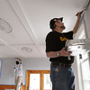 Salem:<br /> Bob Drinkert, Home Depot personnel, paints the wall in the livingroom during the community renovation project at the Plummer Home for Boys in Salem on Thursday.<br /> Photo by Ken Yuszkus/Salem News, Thursday, April 21, 2011.
