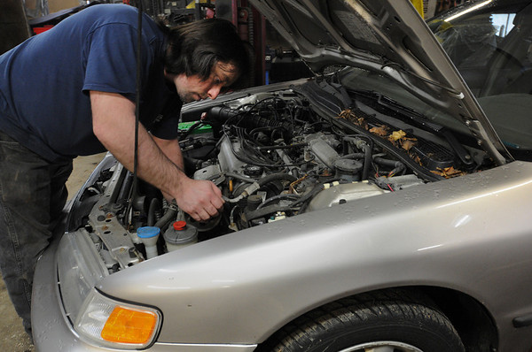 Salem:<br /> Jim Sully, of SS Automotive, checks under the hood of an automobile at the garage.<br /> Photo by Ken Yuszkus/Salem News, Thursday, March 4, 2010.