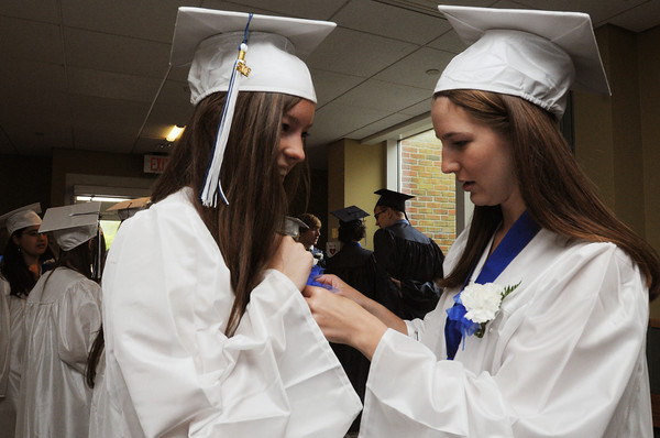 Wenham:<br /> Tess Obenschain has help with pinning on her flower corsage by Sarah Henkels prior to the procession of the Hamilton-Wenham Regional High School graduation held at Gordon College.<br /> Photo by Ken Yuszkus/Salem News, Sunday, June 3, 2012.