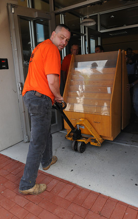 Peabody:<br /> Kevin Guzofski of the Peabody DPW removes a bookcase from the old Borders Books building to be loaded onto a truck.. <br /> Photo by Ken Yuszkus/The Salem News, Thursday, August 16, 2012.