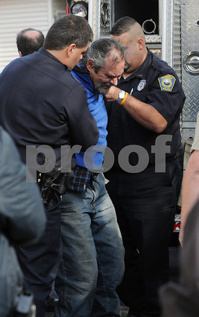 Beverly:<br /> Beverly police raise Roberto Yapor after placing handcuffs on him. He climbed to the peek of the roof of the United Methodist Church. Many onlookers watched as police and fire personel got him down. <br /> Photo by Ken Yuszkus/Salem News, Monday October 6, 2008.