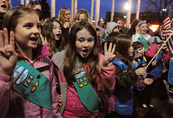 Salem:<br /> From left, Girl Scouts, Caroline Vozzo, Alexandra Ambler and her twin sister Madelyn Ambler, recite the Girl Scout pledge to celebrate the 100th anniversary of the organization. The group gathered near the flag poles across from the Salem Post Office.<br /> Photo by Ken Yuszkus/Salem News, Monday,  March 12, 2012.