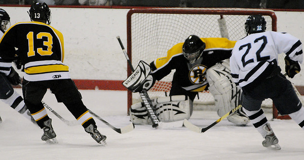 Peabody:<br /> Bishop Fenwick's goalie Brad Rocheville stops the puck from Peabody's Nico Manganiello during the Bishop Fenwick vs Peabody 24th annual Carlin Cup hockey game at the McVann-O'Keefe Rink in Peabody.<br /> Photo by Ken Yuszkus/Salem News, Monday, February 21, 2011.