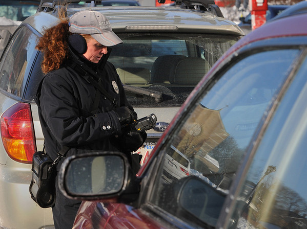 Salem:<br /> Gloria Merrill, parking enforcement officer, writes a parking ticket for a vehicle parked at an expired parking meter.<br /> Photo by Ken Yuszkus/Salem News, Wednesday, December 23, 2009.