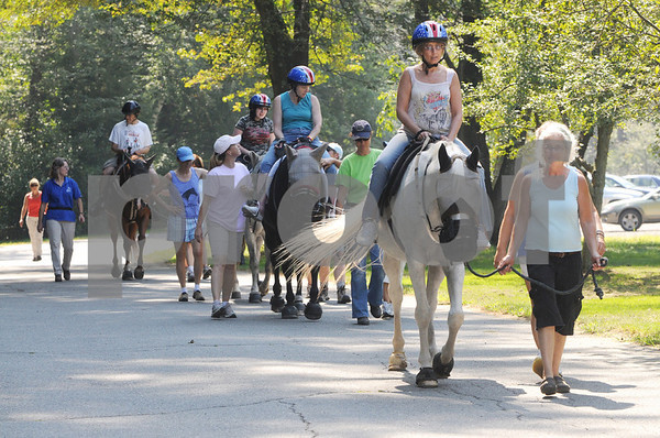 Topsfield:<br /> Laura White of Danvers rides Cadance, with Andrea Mozur of Danvers leading the horse, as the group starts their ride. The free program for physically disabled people to be able to ride a horse was held at the Bradley Palmer State Park.  <br /> Photo by Ken Yuszkus/Salem News Friday, September 05, 2008