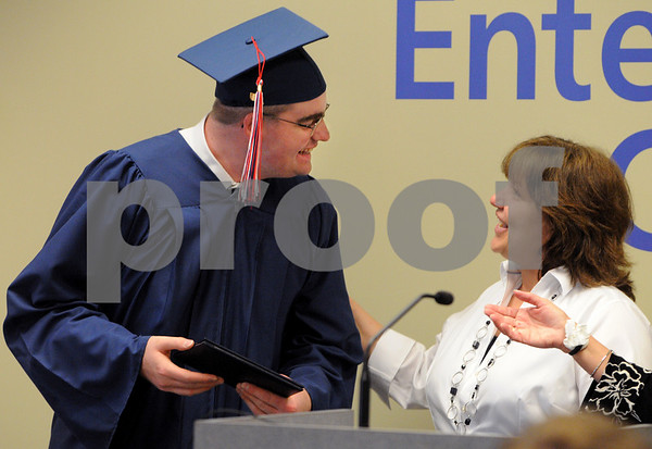 Salem:<br /> Max Cullen receives his diploma and a few words from Christine McAlpine. He is graduating from the Embark Program during the graduation ceremony at Salem State College Enterprise Center.<br /> Photo by Ken Yuszkus/Salem News, Tuesday, June 16, 2009.