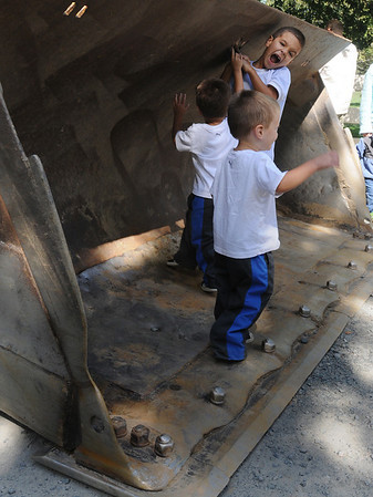 Danvers:<br /> Brett Baldassare, 7, hangs from a hook inside the bucket of a bucket loader on display during Truck Day at Endicott Park in Danvers on Saturday. His twin brothers, Brady and Michael, 3, are also standing in the bucket.<br /> Photo by Ken Yuszkus/Salem News, Saturday,  September 11, 2010.