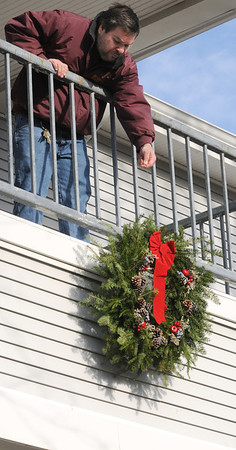 Beverly:<br /> Chip Palmer, building manager, hangs a wreath with wire from the railing of the second floor in the front of the Council On Aging Senior Community Center<br /> Photo by Ken Yuszkus/Salem News, Tuesday, December 13, 2011.