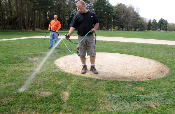Wenham:<br /> Wenham DPW workers Shawn Davis, right, waters the new turf by a pitcher's mound at Pingree Park with the help of Bob Viel, to have the field ready for the little league season which starts on Monday.  The new turf needed watering to survive the dry weather conditions. The Wenham DPW has worked hard to have all twelve ball fields in town ready.<br /> Photo by Ken Yuszkus/Salem News, Wednesday, April 18, 2012.