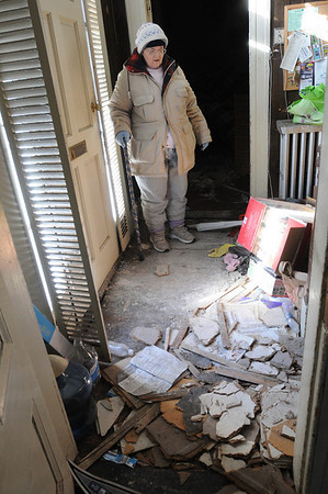 Salem:<br /> Mary Ahearn looks at the mess in the hallway which was the result of the fire in her home at 4 Buffum Street on December 18.<br /> Photo by Ken Yuszkus/Salem News, Wednesday, December 30, 2009.