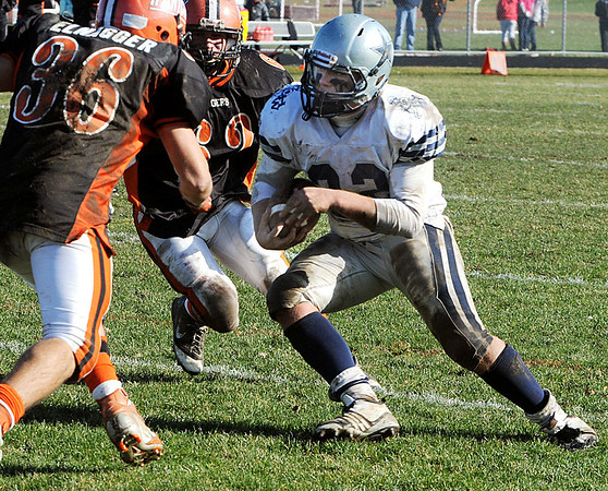 Ipswich:<br /> Hamilton-Wenham's Elliott Burr runs the ball with Ipswich's John Elnagger, left, and Peyton Primack, center, ready to tackle him during the Hamilton-Wenham at Ipswich football game on Thanksgiving Day.<br /> Photo by Ken Yuszkus/Salem News, Thursday, November 24, 2011.