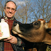 Ipswich:<br /> David Beardsley, farm director, holds a half gallon bottle of milk on sale at Appleton Farms. Mimi, a Jersey cow, checks it out.<br /> Photo by Ken Yuszkus/Salem News, Friday, December 9, 2011.