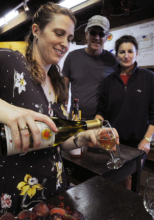 Ipswich:<br /> Miranda Russell of Russell Orchards pours a glass of cider which is one of the varieties of wines that the business creates for William and Carolyn Patrick of Ipswich to taste.<br /> Photo by Ken Yuszkus/Salem News, Friday, July 20,  2012.