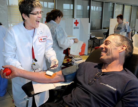 Danvers:<br /> Cathy Lane, collection specialist for the American Red Cross, and John Jermyn, employee of Honda North, share a laugh as John donates blood at the blood drive at Honda North on Wednesday afternoon.<br /> Photo by Ken Yuszkus/Salem News, Wednesday, October 19, 2011.