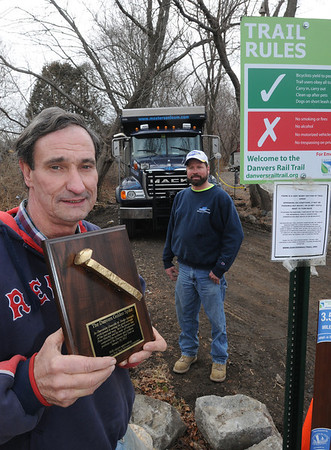 Danvers:<br /> Peter Hinchey won the golden spike award for finishing the last wet stretch of the Danvers Rail Trail. In back of him is Mark McCullum, truck driver for Jeff Masterson. Jeff Masterson donated equipment to haul crushed stone, which was donated by Northeast Nursery.<br /> Photo by Ken Yuszkus/Salem News, Thursday,  February 23, 2012.