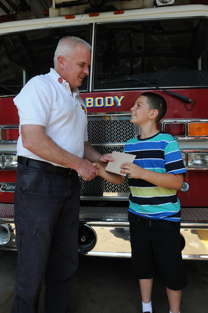 Peabody:<br /> Peabody deputy fire chief Joe Daly accepts a $250 dollar donation from student Justin Dicciso who represents the Northshore Education Consortium. The school raised money for the James Rice foundation, in memory of the Peabody firefighter who lost his life in December while fighting a fire.<br /> Photo by Ken Yuszkus/Salem News, Friday, June 8, 2012.